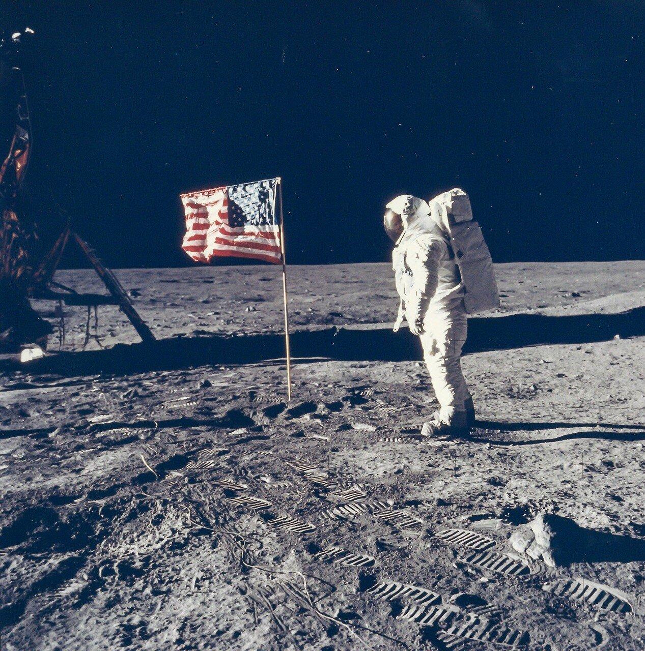 Телескопический флагшток заело, и он не выдвинулся на полную длину. На снимке: Базз Олдрин позирует фотографу рядом с флагом США