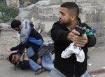 Сотрудник израильской полиции в штатском во время столкновений в Восточном Иерусалиме. 16 марта, пригород Иерусалима Wadi al-Joz, Израиль. Фото Baz Ratner  An undercover Israeli police officer holds a weapon during clashes in East Jerusalem