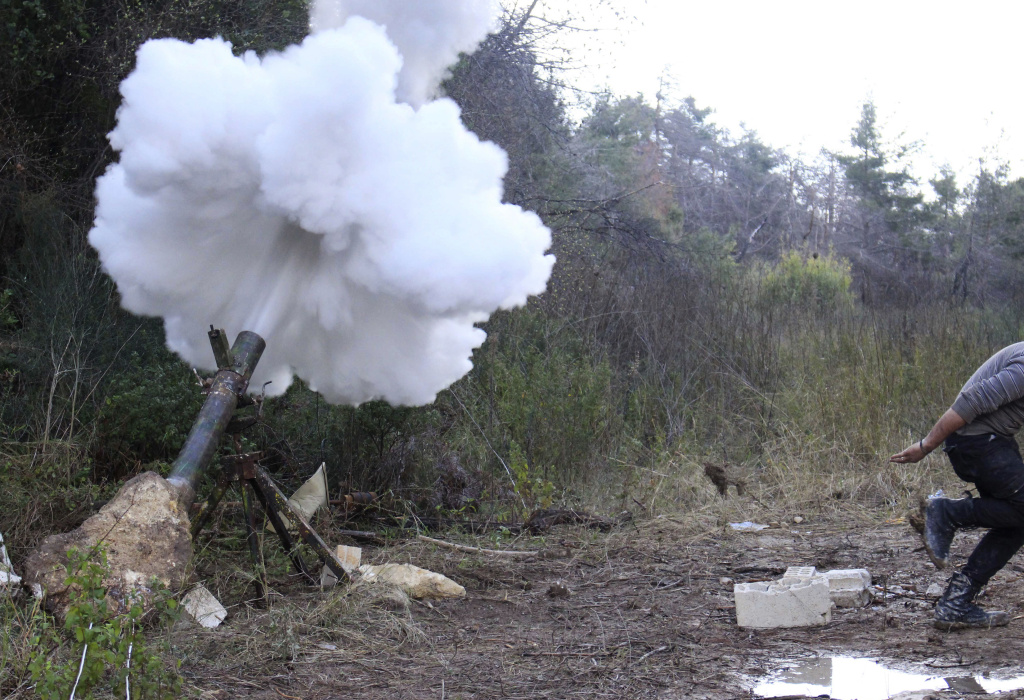 A Free Syrian Army fighter runs to take cover after launching a mortar towards forces loyal to Syria's President Bashar al-Assad in the Jabal al-Akrad area in Syria's northwestern Latakia province