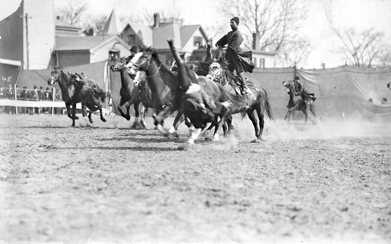 Russian Georgian Cossacks performs tricks while riding horses in a dirt arena for Buffalo Bill's Wild West Show.1901