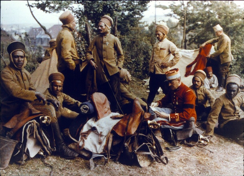 """A photograph of French colonial troops [""""Spahis''] sometime after 1915. The Spahis were light cavalry units recruited from French colonies in Africa, including present day Tunisia, Algeria, Morocco, Senegal, and Cameroon. Seated on a saddle is a French of"""