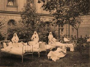 Сестры милосердия и тяжелораненые офицеры в саду лазарета.