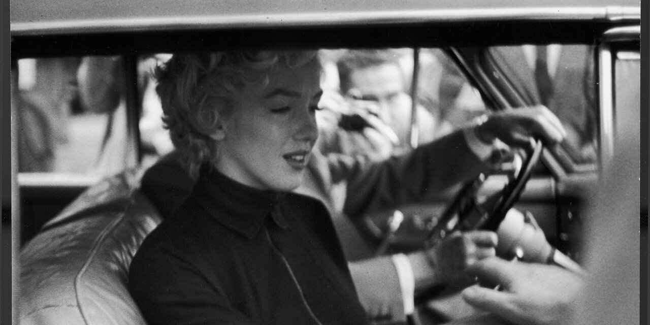 Tearful actress Marilyn Monroe in passenger seat of car beside her lawyer Jerry Giesler after announcing her divorce fr. baseball great Joe DiMaggio.