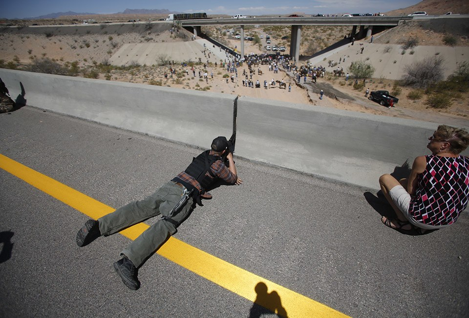 Parker from central Idaho aims his weapon from a bridge as protesters gather by the Bureau of Land Management's base camp near Bunkerville
