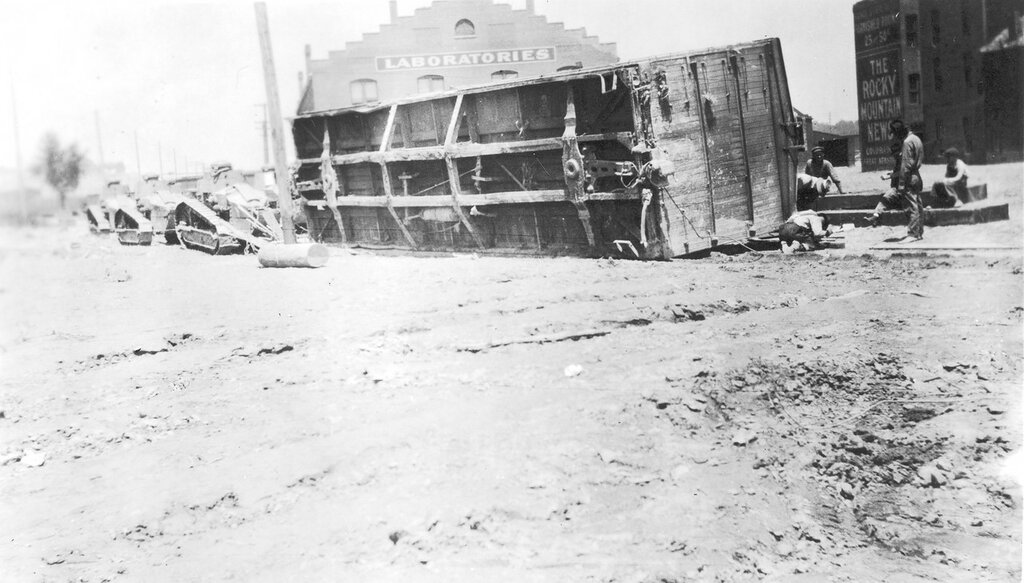 Six army tanks haul an overturned freight car on probably Union Street in Pueblo, Colorado, after an Arkansas River flood. 1921