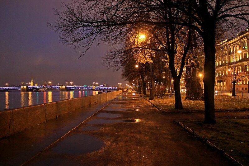 Ночная осенняя аллея на Адмиралтейской набережной в Санкт-Петербурге и вид на Дворцовый мост.