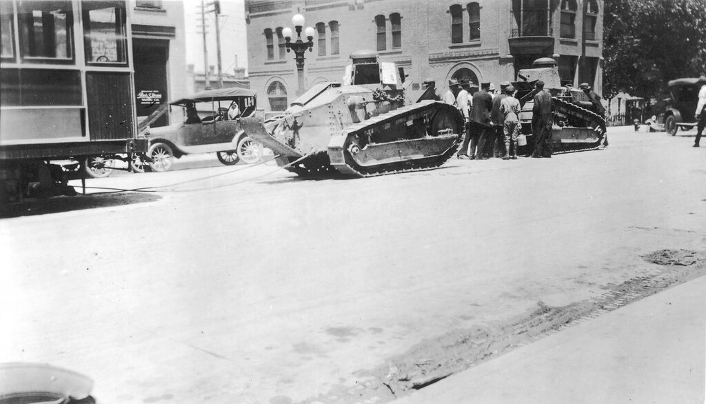 U.S. Army tanks hooked to a streetcar in the central business district of Pueblo, Colorado. The tanks were used to clear the streets after the Arkansas River flood. 1921 June