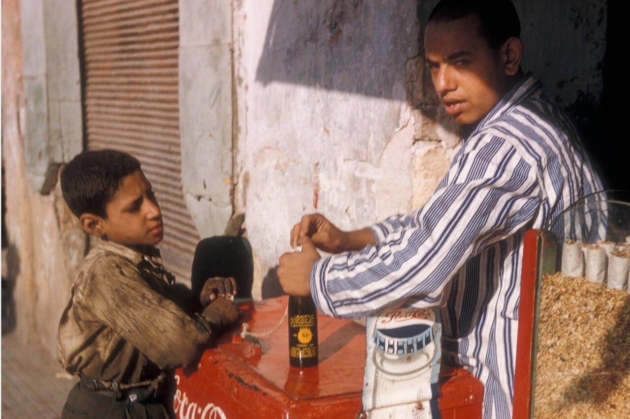 Мальчик покупает безалкогольный напиток у уличного торговца