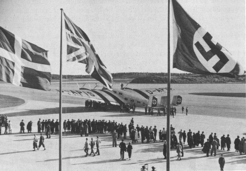 Opening ceremony of Bromma Airport in Sweden with the flags of Denmark, Great Britain and Nazi Germany in the foreground and a Junkers G-38 (which was the largest land-based airplane when it was first built) 1936.jpg