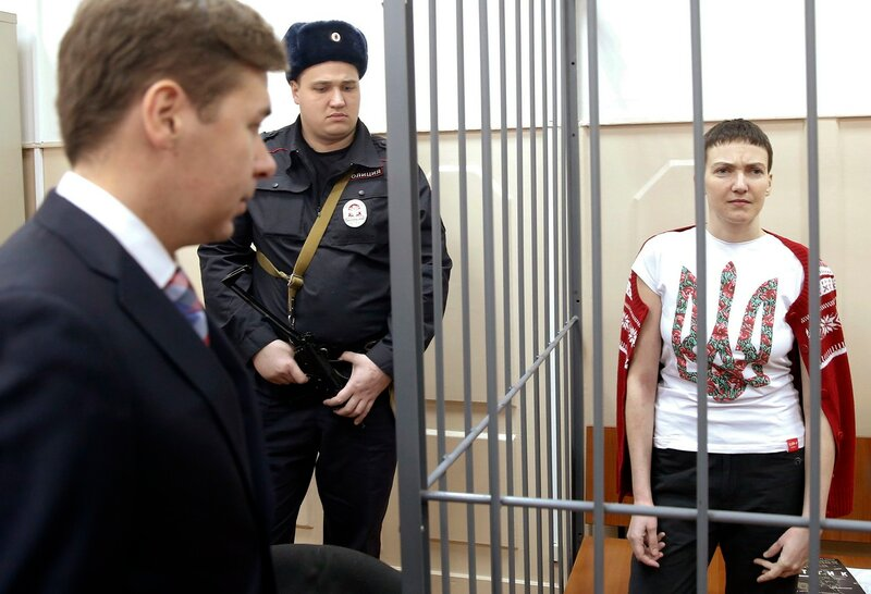 Ukrainian army pilot Nadezhda Savchenko looks out from a defendant's cage during a hearing at the Basmanny district court in Moscow