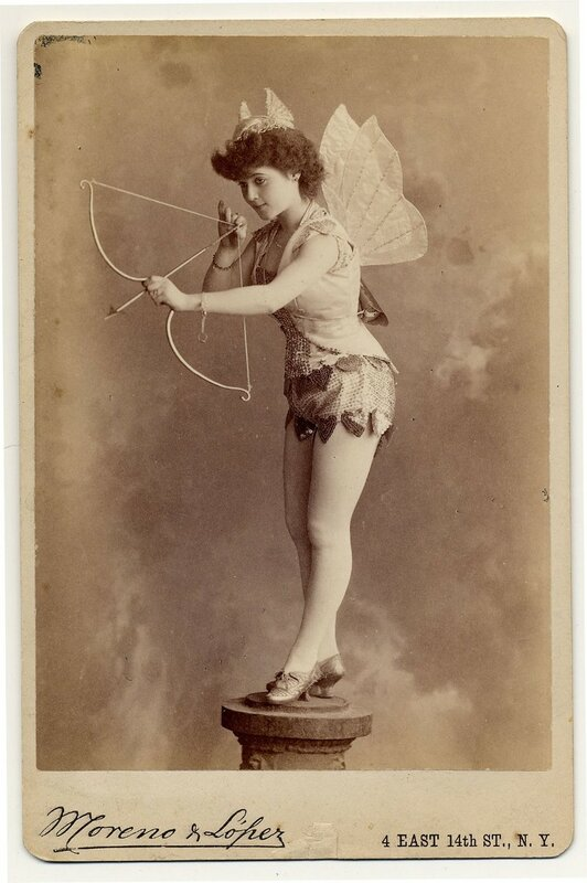 1890. Miss Murdock on pedestal, with fabric wings and horns shooting a bow and arrow.