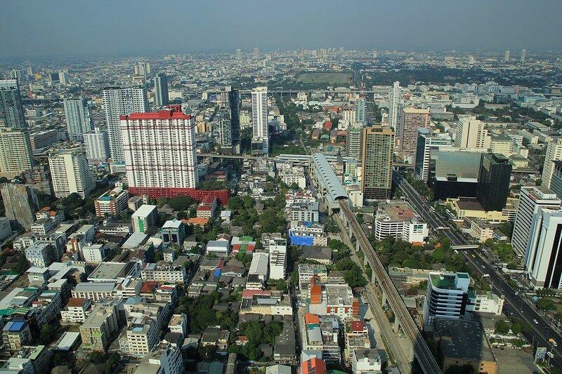 Вид на небоскрёбы, магистрали, станцию легкого метро и парки Бангкока (столицы Таиланда) из небоскрёба Baiyoke Tower II в дневное время