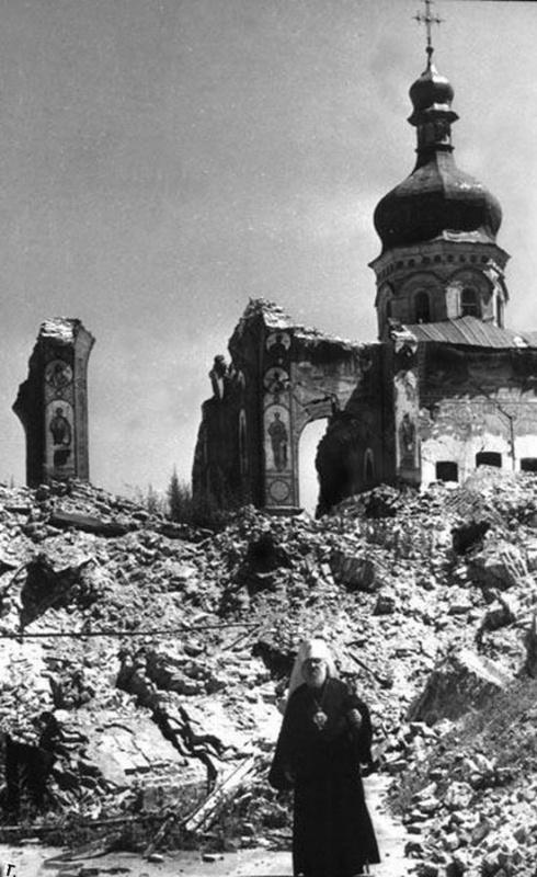 Священник рядом со взорванным Успенским собором в Киеве
