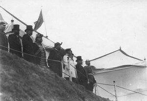 Французский президент Раймон Пуанкаре с группой русских и французких офицеров на царском валике во время парада войск Красносельского гарнизона .