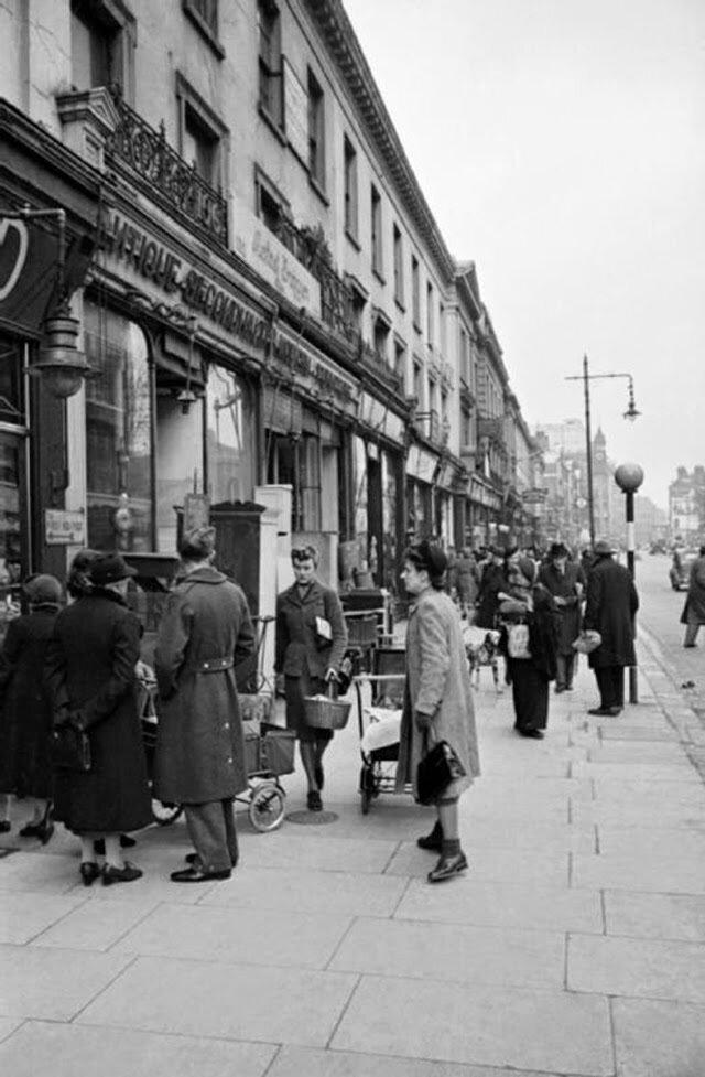 17. После обеда, Оливия посещает магазин на Кингз-роуд в  Челси. Она проходит мимо члена RAF и нескольких женщин с колясками, стоящих в очереди у большого мебельного магазина