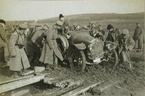 Солдаты одной из армейских частей помогают вытаскивать из грязи автомобиль.