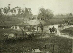Солдаты одной из армейских частей переправляют повозки с полковым имуществом в брод через реку.