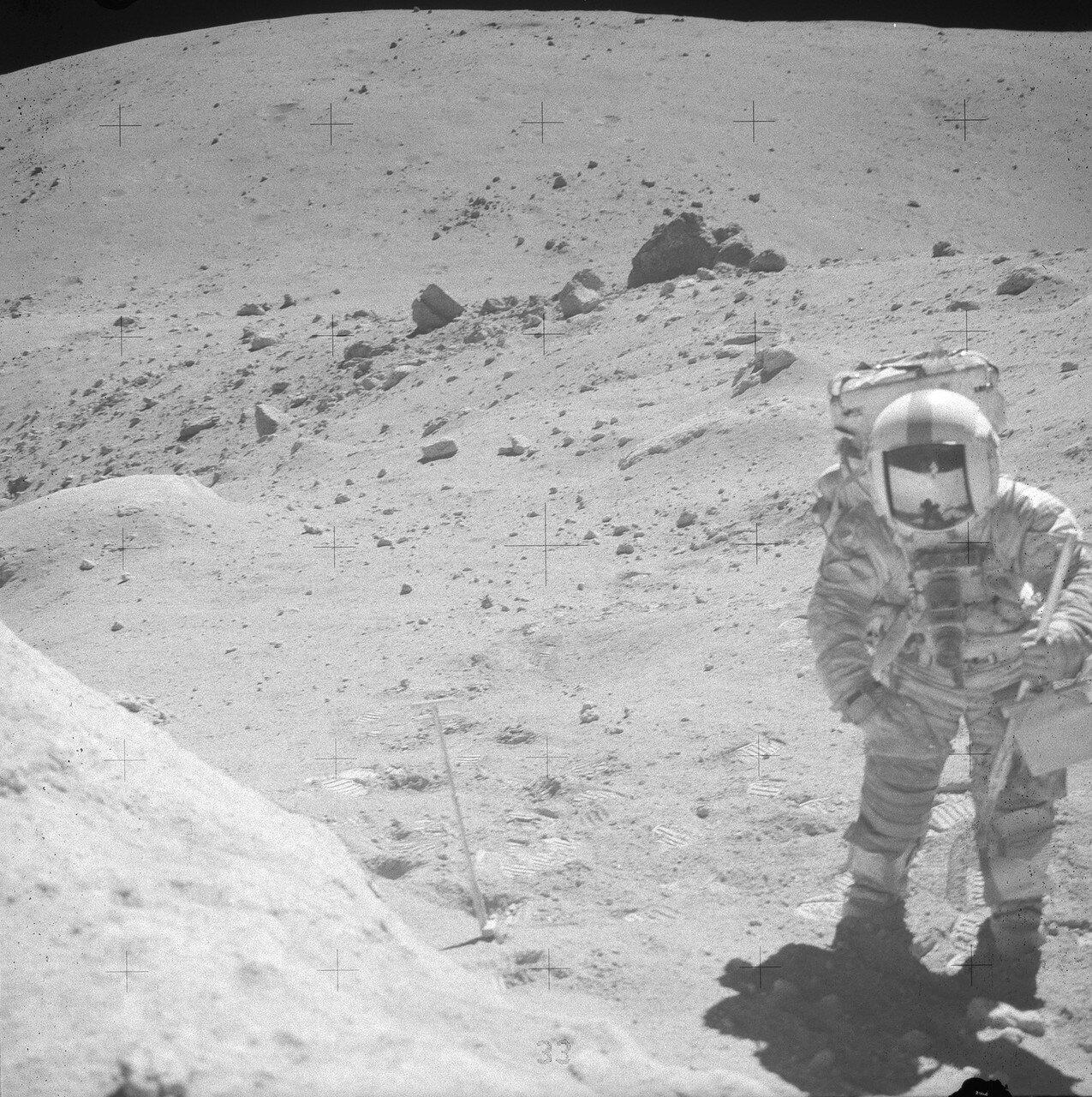 Затем Хьюстон попросил астронавтов взять граблями образец грунта. На снимке: Джон Янг на Station 11. Позади него и чуть левее — скала House Rock. На заднем плане — гора Смоки