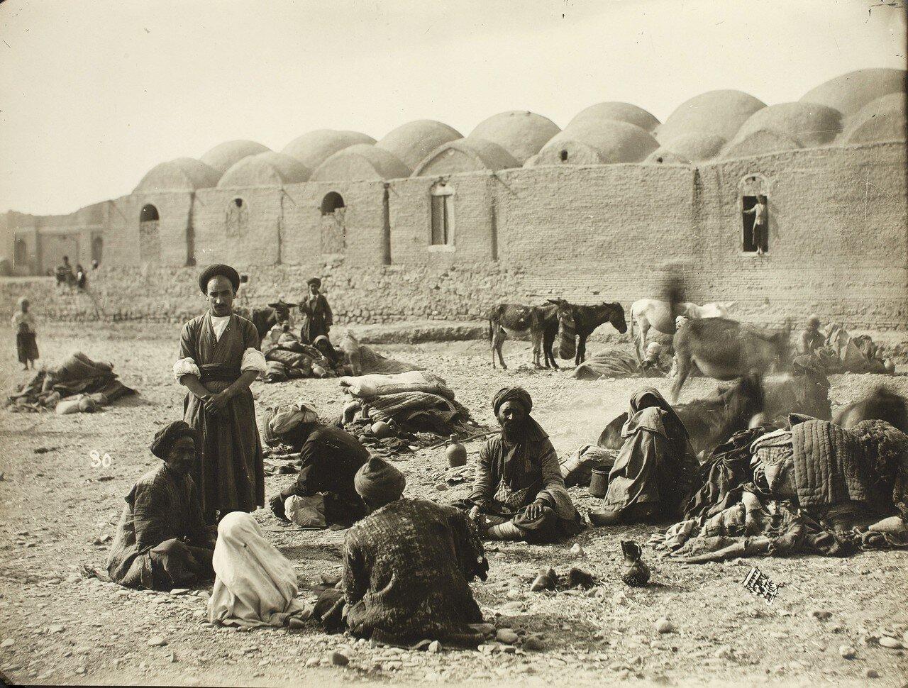 Мужчины и лошади за стенами караван-сарая