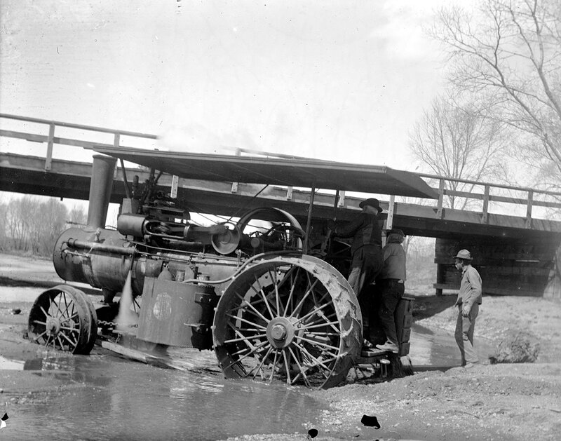 Industries construction equipment steam tractor in shallow water in the South Platte River near the Alameda Avenue bridge in Denver, Colorado, 1909