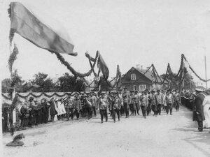 Императоры Николай II, Вильгельм II и сопровождающие их лица проходят мимо встречающих их жителей города.