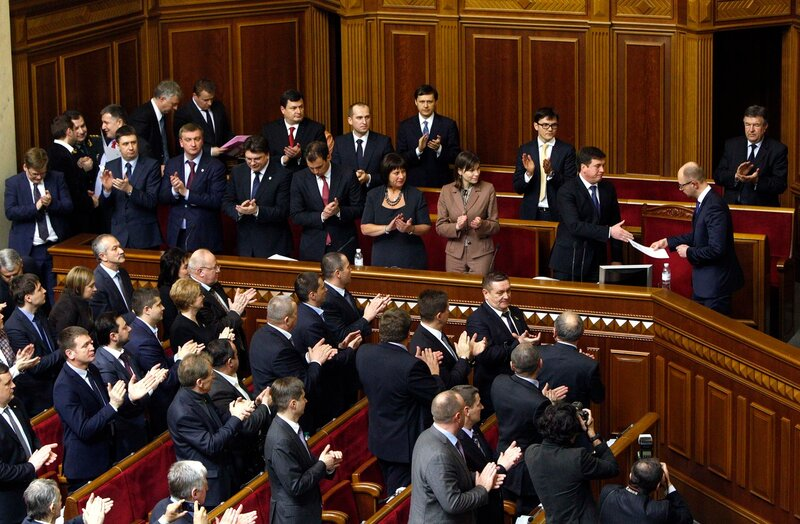 Deputies of Ukrainian parliament applaud for Prime Minister Arseny Yatseniuk and newly appointed ministers during a parliament session in Kiev
