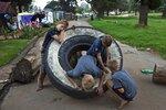 Дети играют с автомобильной покрышкой, используемой для блокировки входа в лагерь-сквот для бедных белых южноафриканцев, 6 марта, Krugersdorp, ЮАР. Фото Finbarr O'Reilly  To match feature SAFRICA-WHITES/