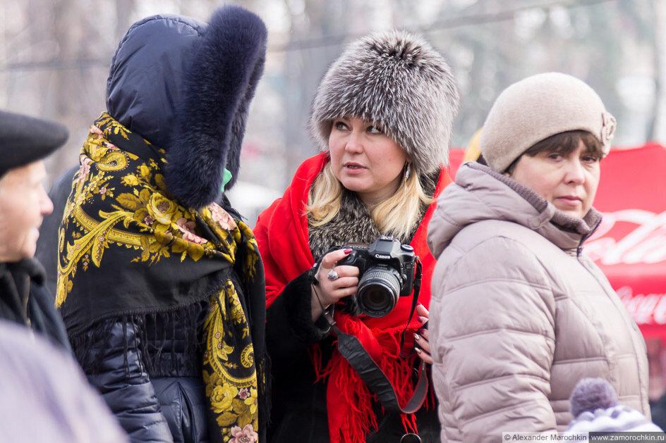 Девушка с фотоаппаратом на праздновании Масленицы
