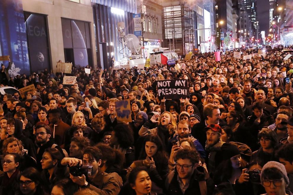 Тысячи жителей Нью-Йорка перекрыли 5-ю авеню возле небоскрёба Трамп-тауэр, 9 ноября 2016 года.