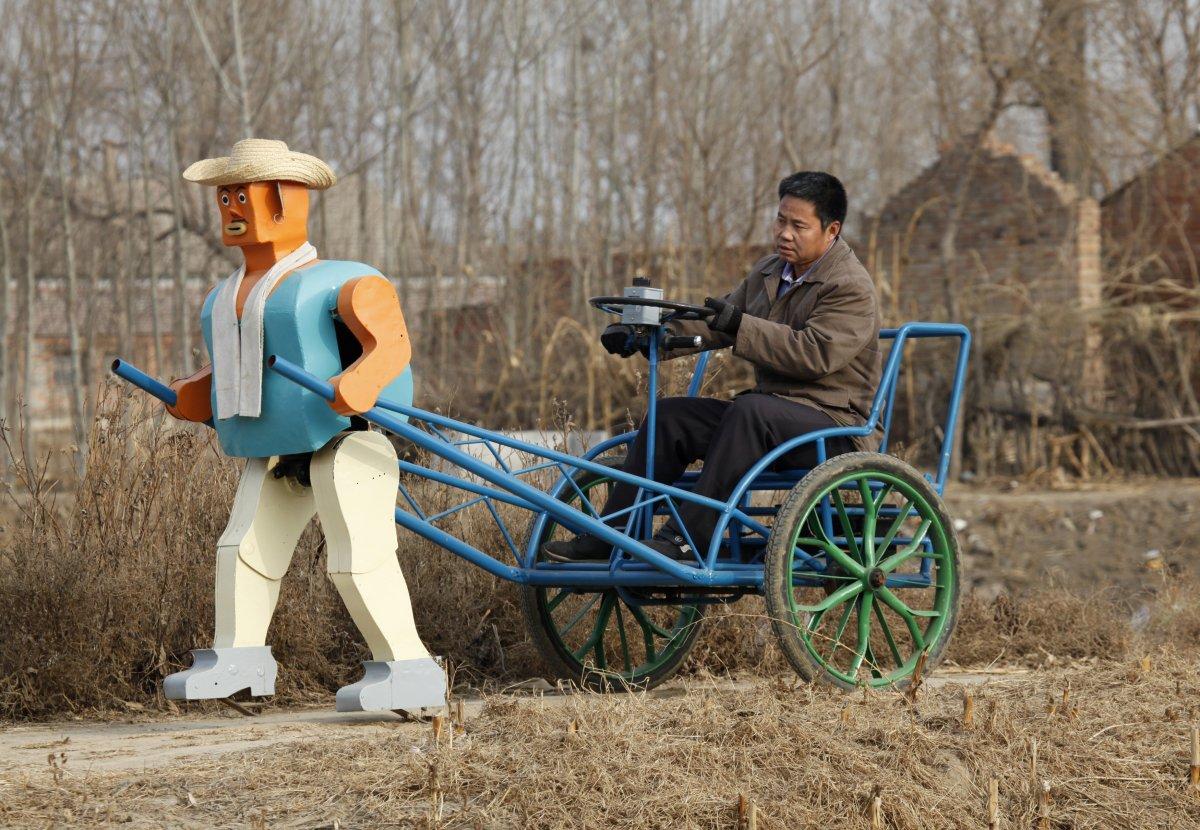 26. Фермер У Юйлу едет на рикше, которого тянет его самодельный робот.