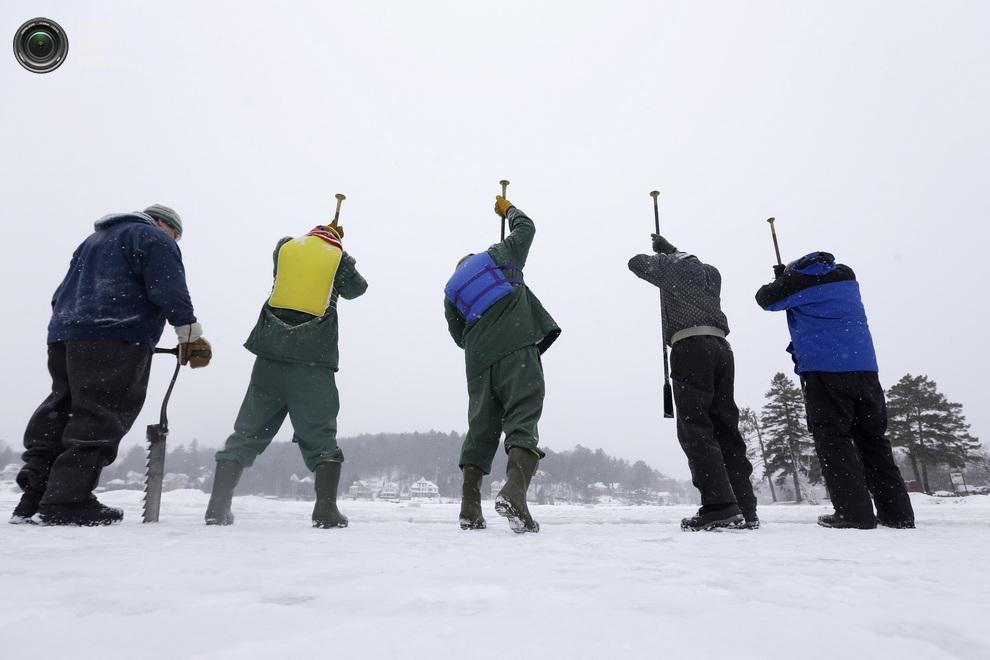 Волонтёры и заключённые в зелёной униформе откалывают блоки льда друг от друга. (AP Photo/Mike G