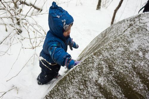 ребенок очищает снег с палатки зимой в походе