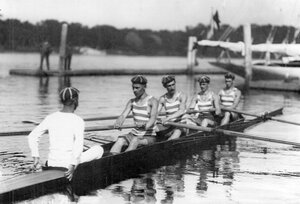 Команда спортсменов с тренером в гоночной лодке у лодочной станции перед началом состязаний