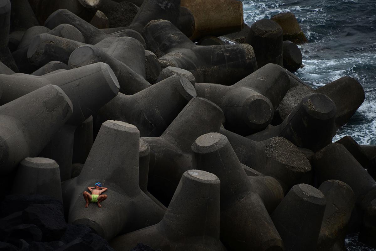 23. Мальчик отдыхает на цементных блоках на маленьком вулканическом острове Стромболи, Италия, 16 ию