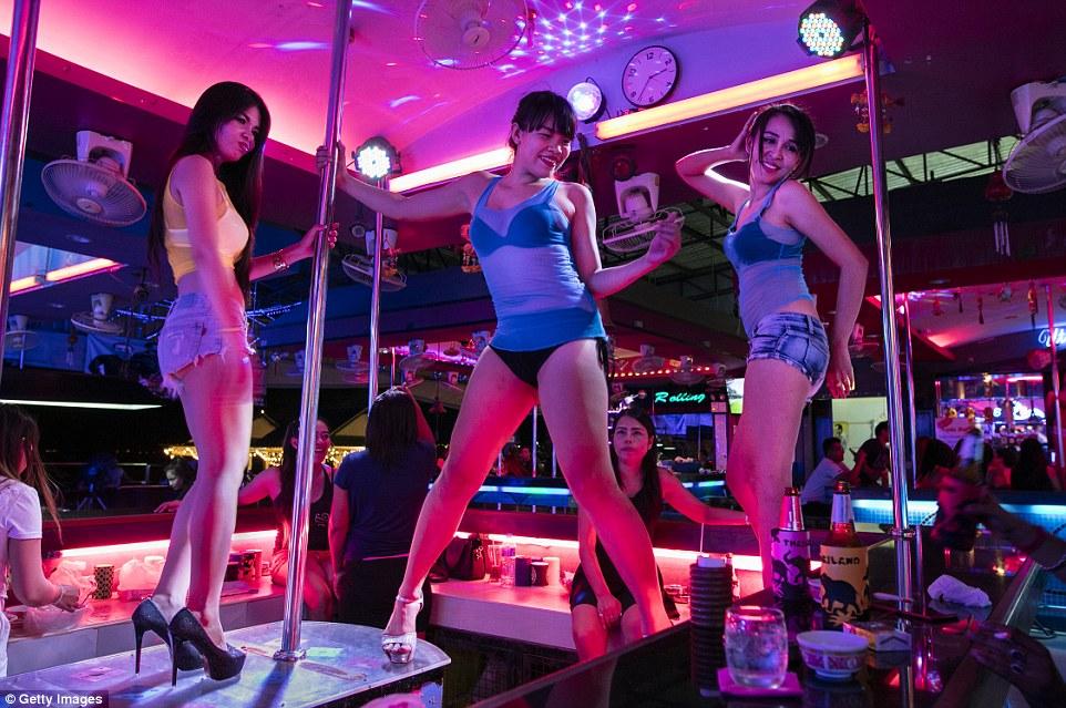 Три женщины танцуют и развлекают мужчин в одном из баров.