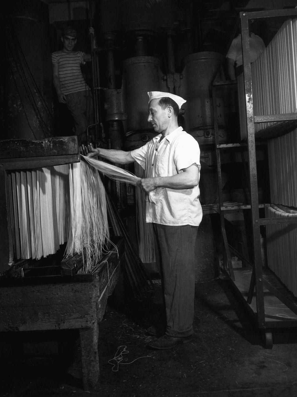Работник Atlantic Macaroni Company развешивает спагетти для сушки на фабрике в Лонг-Айленд-Сити, Нью