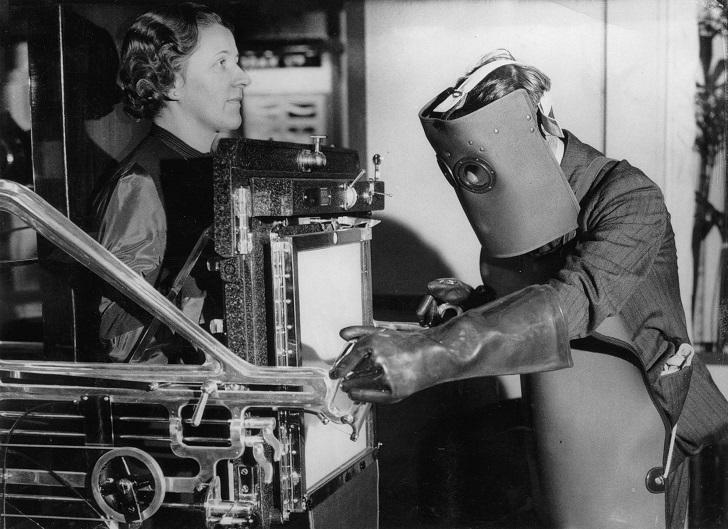 Новейший аппарат рентгена, которым управляет врач-рентгенолог в защитном костюме старого типа. Выста