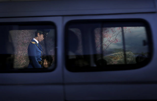 A North Korean traffic police woman is framed by a window of a passing vehicle as she walks past com