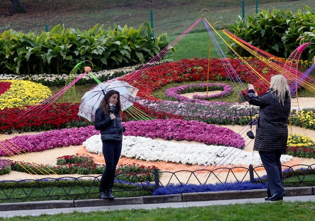 A woman with umbrella poses for a picture during a visit to a flower exhibition on a rainy autumn da