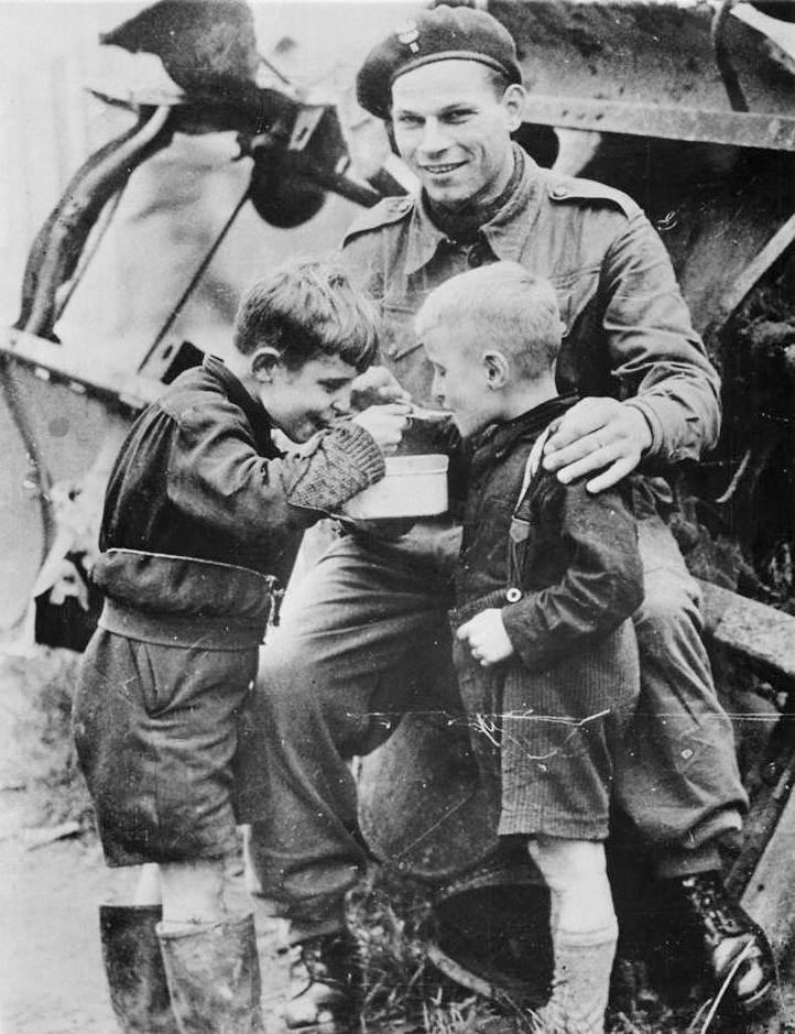 Солдат польских частей Британской армии кормит двух мальчиков.