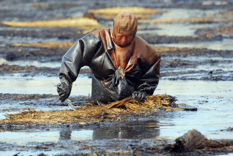 15. Рабочий убирает разлившуюся нефть, порт Далянь, Ляонин