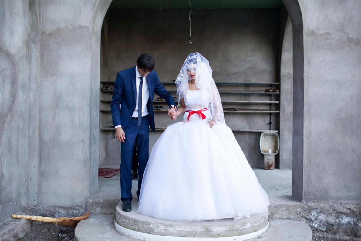 Пара молодоженов-мусульман из азербайджанской диаспоры позирует перед мечетью в день свадьбы. Когда