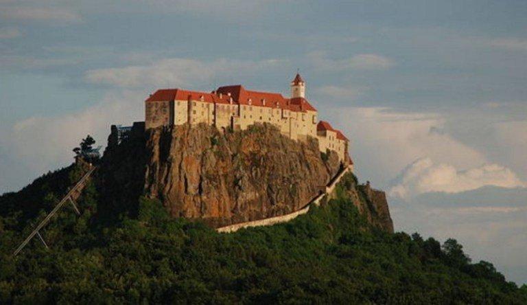 Не так часто можно увидеть замок, расположенный на вершине скалы. Но этот находится даже не на верши