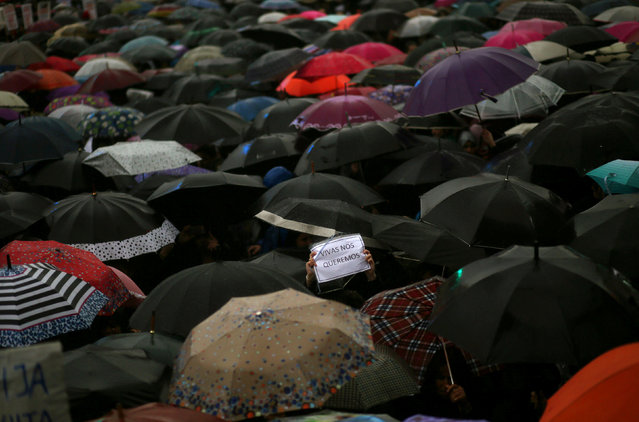 "A woman holds up a sign that reads ""We want us alive"" amongst umbrellas during a demonstration to de"