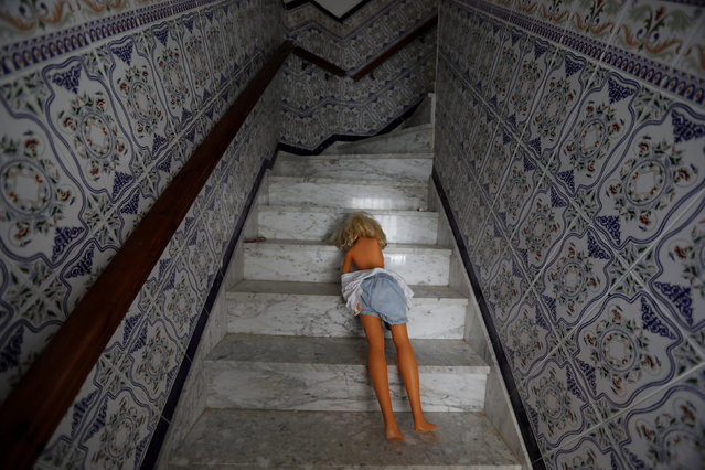 A doll lies on the stairs of a house in the white village of Setenil de las Bodegas, southern Spain