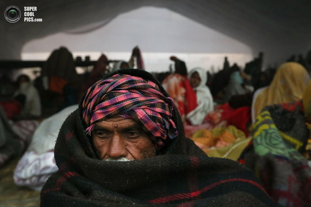 Мужчина греется, укутавшисьпледом. В Индии сейчас прохладно. (AP Photo/Manish Swarup)