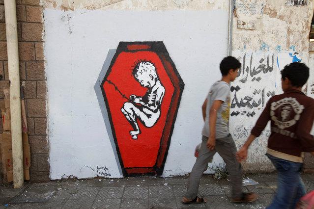 Boys walks pass a graffiti of artist Murad Subai depicting a child suffering from malnutrition in a