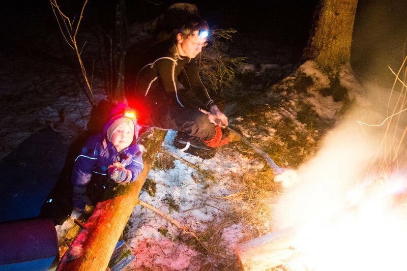 папа и ребенок зимой в походе у костра
