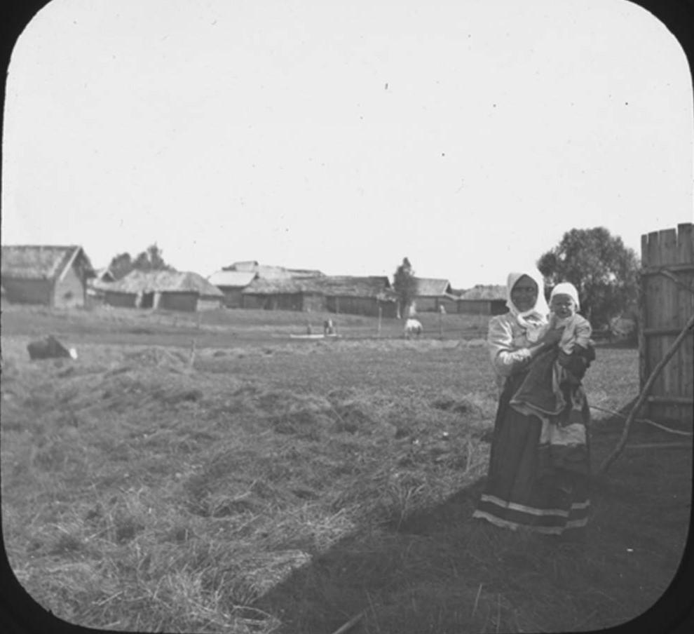 23. Женщина стоит в тени на правой части фотографии с ребенком на руках. На заднем плане деревня Рыльково