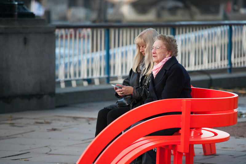 Elderly woman with adult daughter sitting on a red bench and watch the Thames